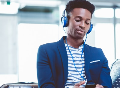 Homem de terno e headphones ouvindo podcasts do Itaú no aeroporto